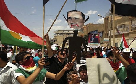 Anti-Syrian regime Kurdish protesters holding an effigy of Syrian President Bashar Assad as they wave their Kurdish flag during a demonstration called the
