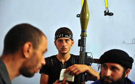 A young Syrian rebel fighter hold a copy of the Koran and a rocket-propelled grenade. Photo: AFP
