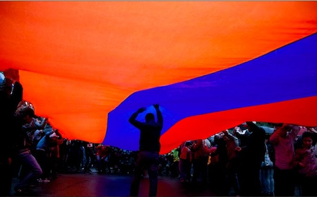 Armenians hold their national flag at the Genocide Memorial in the capital Yerevan. Photo: aspar.com