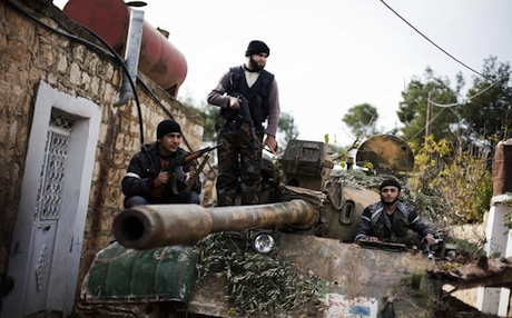 Kurdish fighters of the FSA are seen on a tank captured from the Syrian army north of Aleppo. Photo: AP