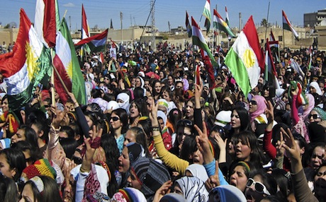 Kurds in the city of Qamishli wave the Kurdish flag as they rally against the Syrian government. Photo: AFP