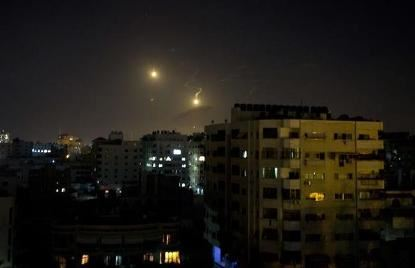 Israeli artillery flares illuminate the sky over Gaza City following an air strike earlier this month. Photo: AFP