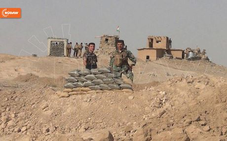 Peshmerga soldiers posing behind a sand-bag position in Kirkuk.